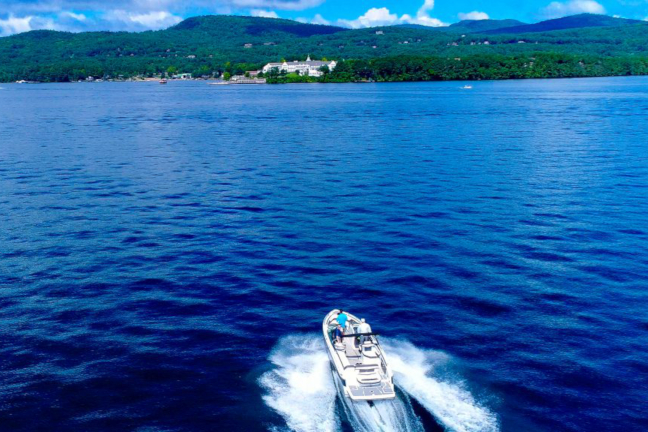 Boat Rental - A bowrider boat driving across the open water of Lake George in New York